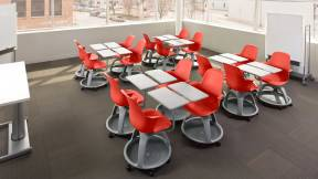 4 clusters of 4 Chili Red Node Desk Chairs with Tripod Base and Work Surface in a classroom setting