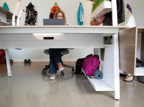 Bivi Bottom Shelf attached to the Bivi Desk frame while a woman works on the desk while a man adjusts a Bivi Planter