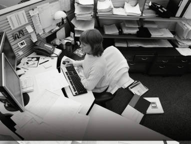 Woman sitting at an unorganzied desk without Universal Storage
