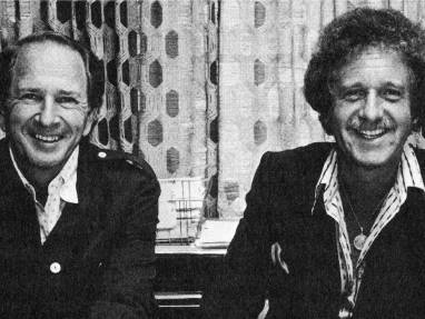 Two men smiling in a black and white photo
