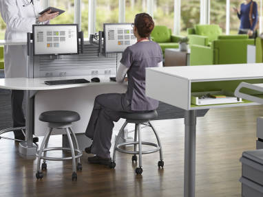 Nurse sitting on Verge stool in front of Sync workstation speaking with a doctor