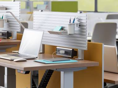 A laptop and other desk accessories are shown on a height-adjustable desk from Steelcase