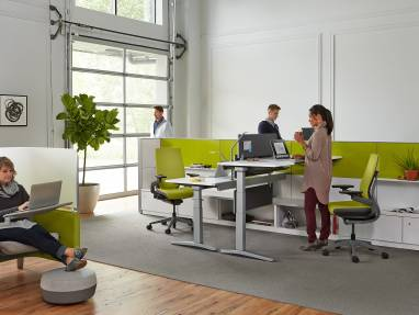 Two Series 5 height-adjustable desks in an open office next to a lounge area