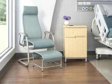 High-back Cura patient chair with a sled base and ottoman in a medical patient room