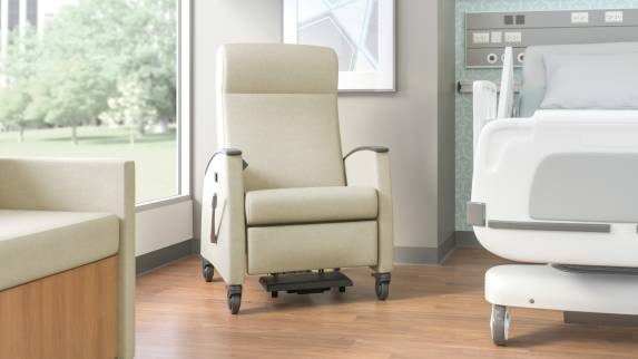 Off-White Mitra Recliner next to a hospital bed in a medical recovery room