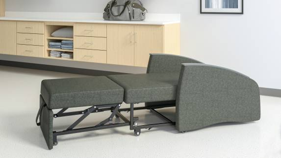 A dark grey Mitra Sleeper fully extended to bed form ina medical room