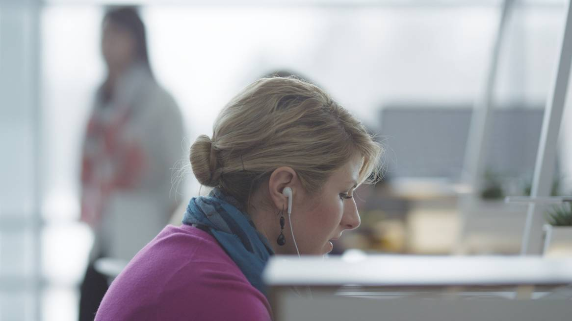 Woman with earbuds in an office