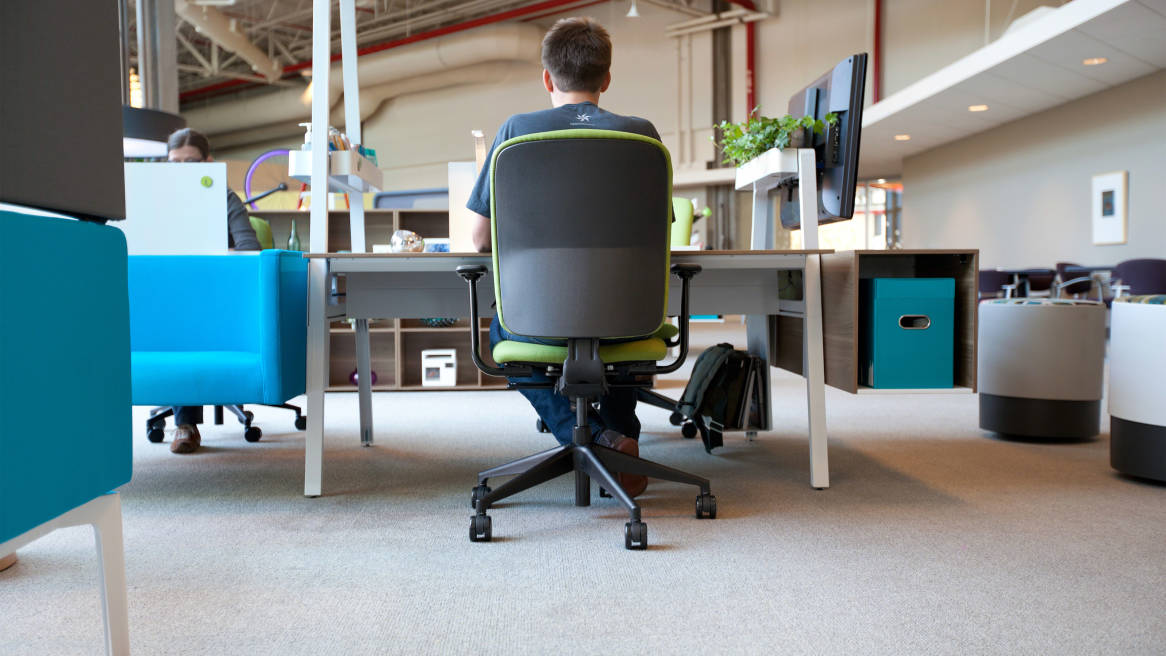Rear view of worker sitting at a Bivi desk in a Green Jack Task Chair