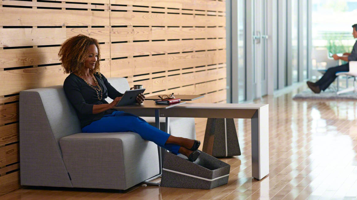 A woman sits on a Campfire Half sofa while using a Campfire Skate table and Campfire Footrest A Campfire Slim table is next to her