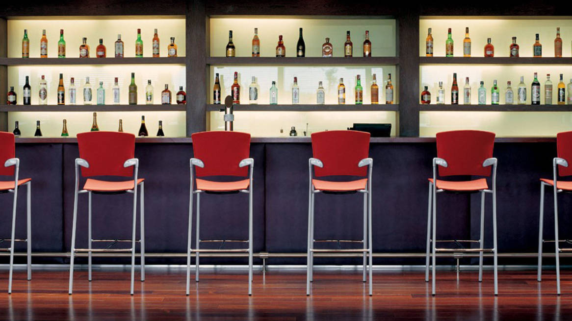 Six Red Enea Bar Stools at a bar