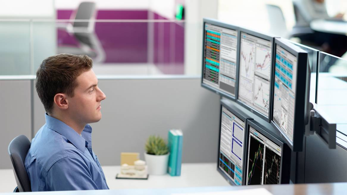 Man sitting at a desk in front of four monitors supported by Plurio