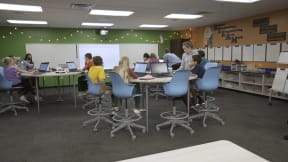 Kids in a classroom collaborating while seated on blue Node stools.