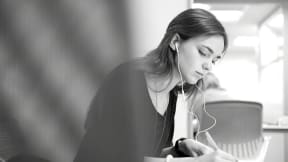 Woman with headphones on while writing something down