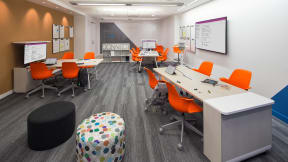 orange Node chairs and wooden table inside a classroom