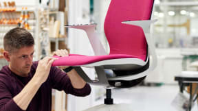 A worker focuses on a SILQ desk chair from Steelcase with bright pink upholstery and white arms and legs
