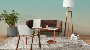 In an office lounge, a Bivi Rumble Seat with brown leather upholstery is shown with a copper table and armchair