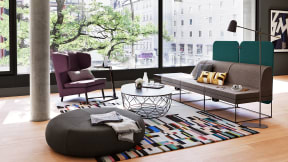 Ancillary space with a brown Turnstone Campfire Lounge on the right, a purple high sofa chair on the left, a black Bolia Comb table and a brown Ronda Pouf on the front of the room.