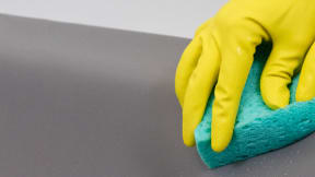 image showing gloved hand cleaning with a sponge