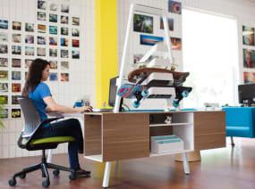 Bivi Board Rack above Bivi Trunk while a woman works on the Bivi Desk