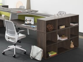 Items are stored on a Bivi 3-High Depot shelf placed at the end of a workstation of Bivi Dual Height desks. Steelcase Series 1 chairs are also seen.