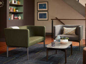 Two Bivi Rumble Seats in green and gray upholstery around a Bassline Table in an office lounge