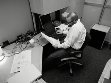 Man on the phone at a crowded desk with exposed cables