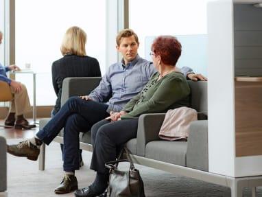 Man and woman sitting comfortably on Regard lounge seating