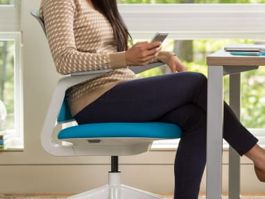 woman on phone and reclining in Cobi Collaborative Chair