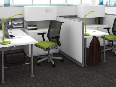 A Kick panel system is used to create two workstations, also featuring TS series storage and Think desk chairs with green upholstery from Steelcase
