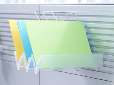PaperFlo Manager attached to a Slatwall holding blue, green, and yellow folders