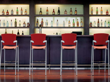 Six Red Enea Bar Stools at a bar