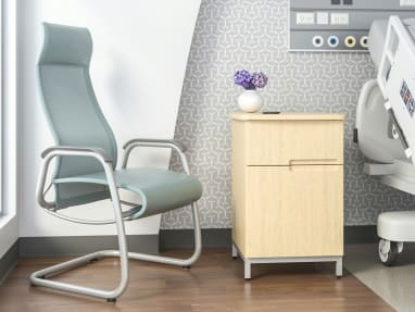 Green high-back Cura patient chair in the corner of a recovery room in front of a window