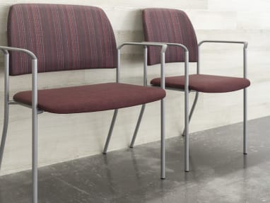 Sorrel Bariatric Stacking Chair next to a Sorrel Stacking Chair against a wall