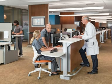 Healthcare professionals work in a space with Cobi desk chairs and a Steelcase Sync desk system