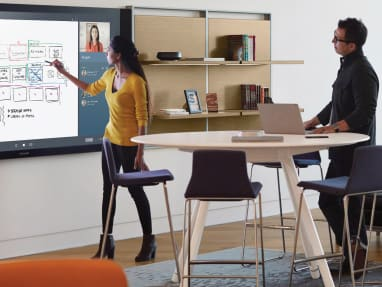 Woman and man collaborating while the woman is drawing on interactive ideation hub surface