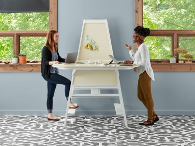 Two women standing a Bivi Standing Desk and Bivi Arch