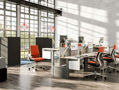 Several workstations are created using Ology height-adjustable benches, Universal center screens, and Gesture task chairs with orange upholstery