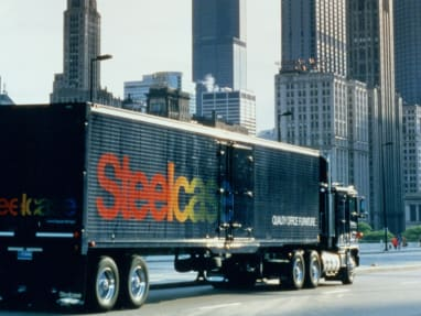 A semi truck with the Steelcase logo drives in a city