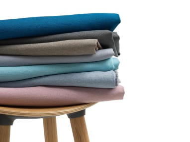 variety of upholstery stacked on stool