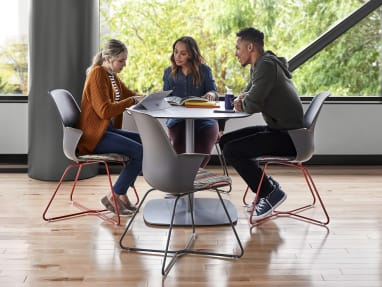 Three people have a conversation at an Enea Lottus Table while sitting on Node X base chairs