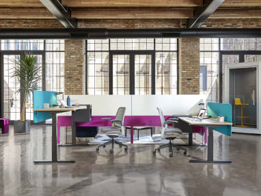 An office environment featuring Migration height-adjustable desks, Steelcase Series 1 chairs, and an Answer Fence. A SnapCab Pod with Coalesse Enea Lottus stool is seen nearby.