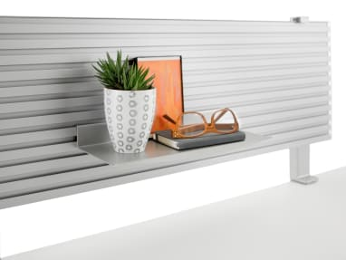 A notebook, glasses and other personal items sit on a small shelf affixed to the slatwall