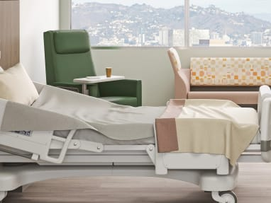 patience room with a green Empath chair, a large sofa and a medical bed.