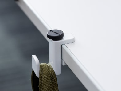 SOTO Personal Hook attached to the edge of a table with a bag hanging on it