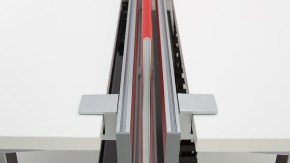 SOTO Rail with a red screen divider in between two white desk surfaces
