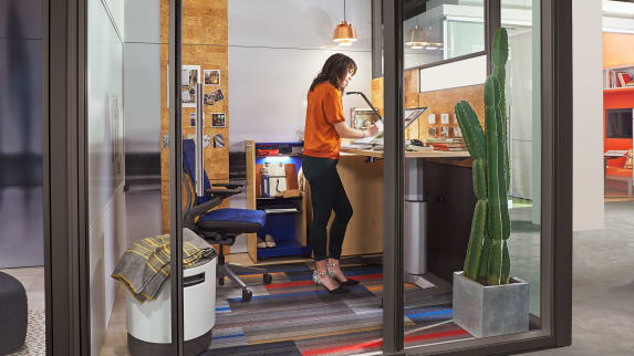 Woman on a creative private work area with adjustable height desk and glass walls
