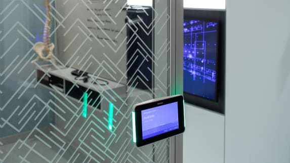 Steelcase Roomwizard scheduling system on a glass wall displays that a conference room is currently available using the screen and LED lights on the side of the tablet