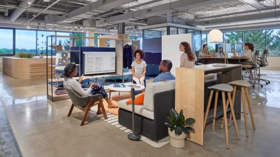 Open-space to informally discuss ideas, equipped a gray lounge sofa, a gray chair and gray Enea Cafe Stools in front of a TV screen.