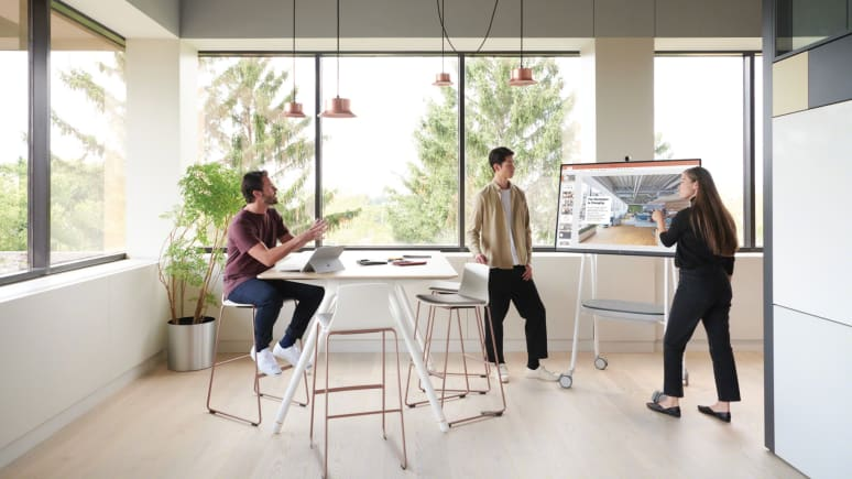 A woman points at a screen displayed on a Steelcase Roam cart close to some Montara stools from and a Potrero415 table from Coalesse