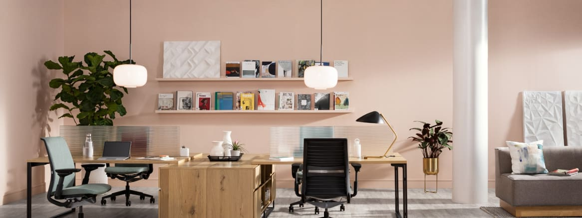 A workstation created with West Elm Work Greenpoint Benching is shown with Steelcase Think desk chairs